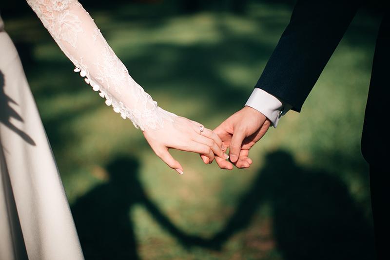 Brud og brudgom holder hender