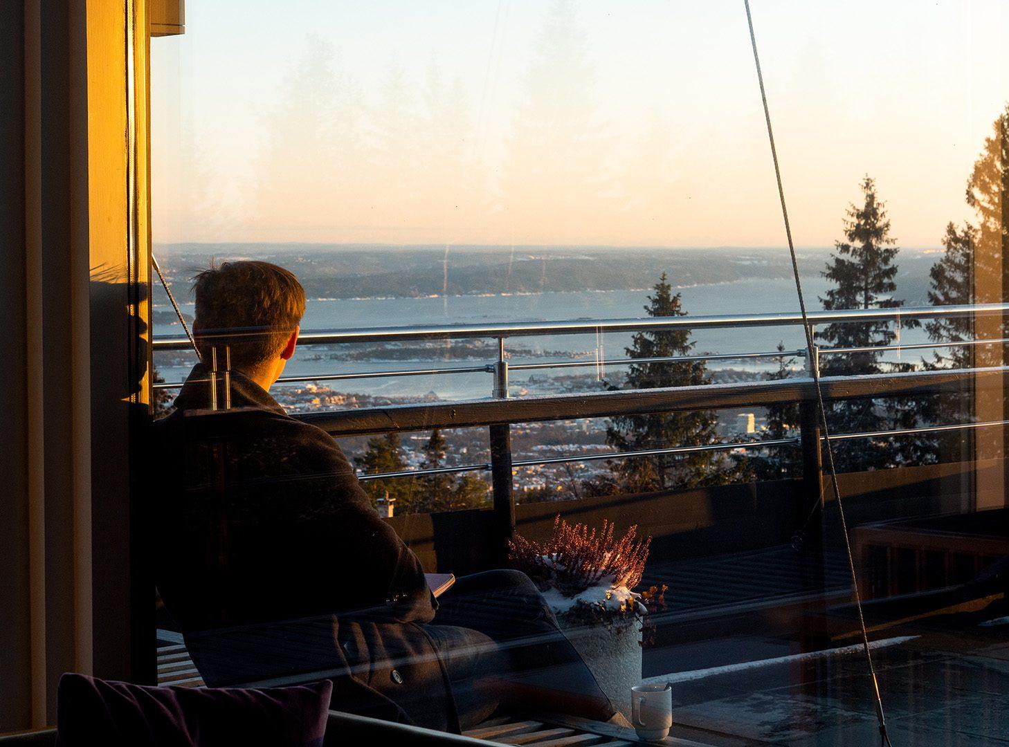 Mann nyter utsikt i solnedgang hos Voksenåsen