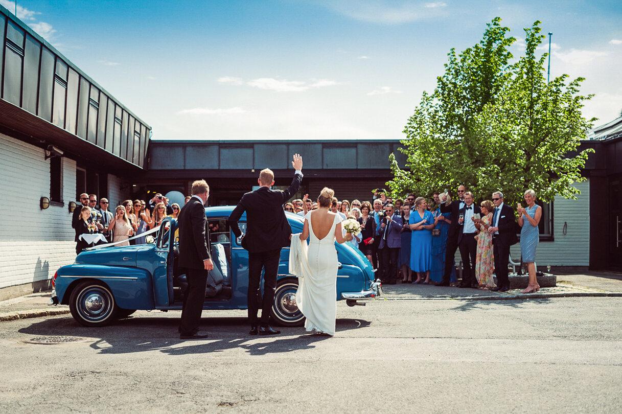 Nygift brudepar vinker til bryllupsgjestene