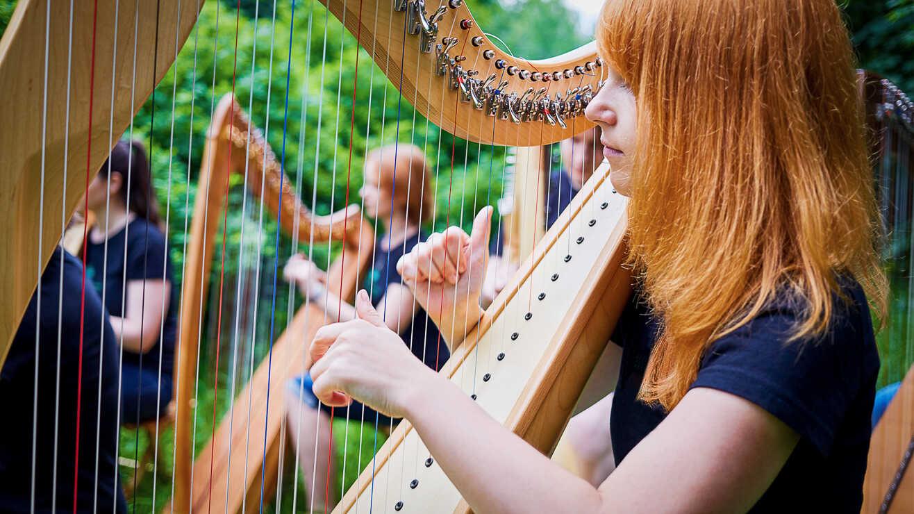 Damer spiller harpe på et arrangement hos Voksenåsen